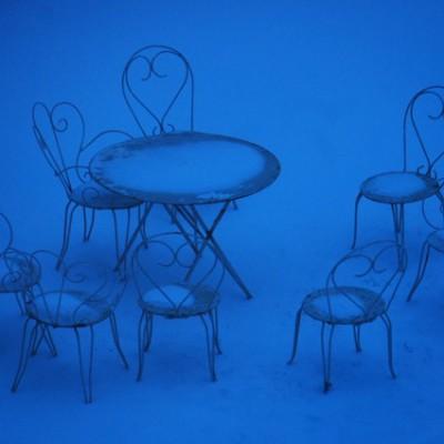 stoeltjes in de sneeuw in avondlicht